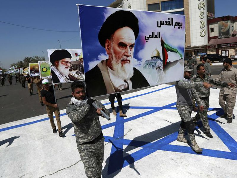 Supporters of Iraqi Hezbollah brigades march on a representation of an Israeli flag with a portrait of late Iranian leader Ayatollah Khomeini and Iran's supreme leader Ayatollah Ali Khamenei, in Baghdad, Iraq. (AP)