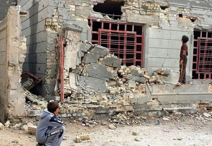 Dos niños iraquíes observan una casa destruída por un ataque del ejército iraquí en Faluya, en el oeste de Irak. (Archivo/EFE)