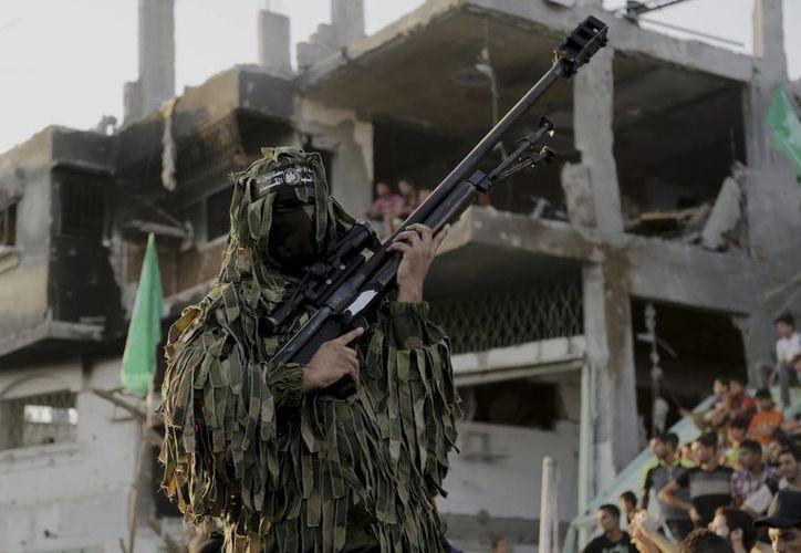Un milciano de las brigadas de Al Qassam es visto en la celebración de  victoria de Hamás sobre Israel, este miércoles en el barrio Shijaiyah, en ciudad Gaza. Israel se declaró hoy vencedor en el conflicto. (Foto: AP)