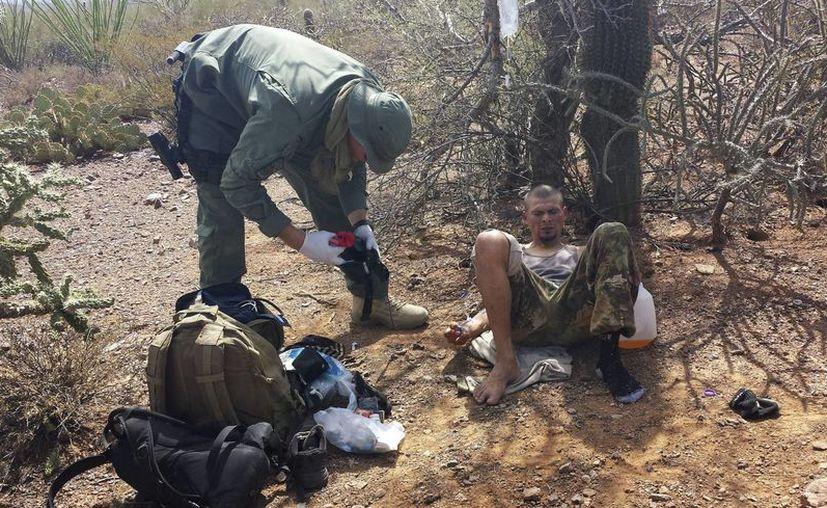 Un agente de la Patrulla de Fronteras asiste a un migrante que fue encontrado deshidratado cuando intentaba cruzar ilegalmente la frontera entre México y Estados Unidos cerca de Sells, Arizona. (AP/Astrid Galvan)