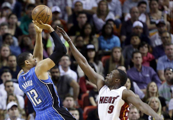 Tobias Harris, del Magic, lanza la pelota por sobre Luol Deng (9), de Heat, durante el segundo lapso del duelo entre ambas escuadras. (Foto: AP)