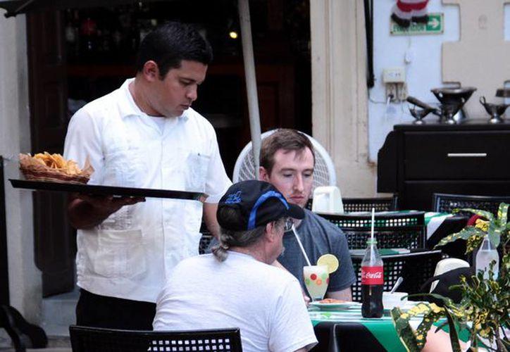 El desplazamiento de las cenas tradicionales en los hogares ha beneficiado al sector restaurantero. Imagen de un mesero mientras atiende a dos hombres, en el Centro de Mérida. (Milenio Novedades)