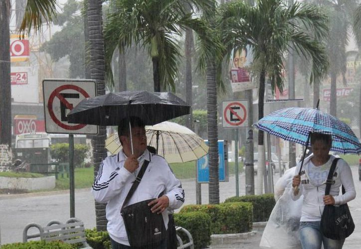 Algunas personas se protegen de la lluvia en medio de inundaciones por el paso de un huracán en el Pacífico mexicano. (Archivo/EFE)