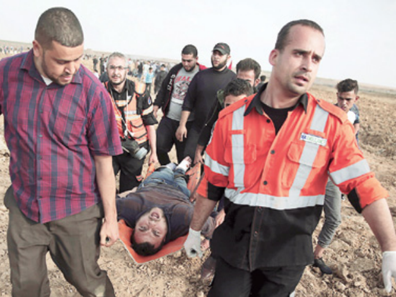 Palestinians medics carry a wounded man during a protest at the Gaza Strip's border with Israel. (AP).