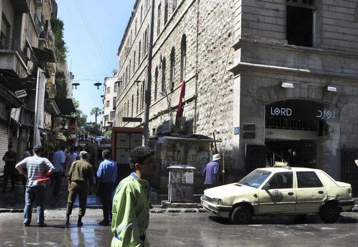 Fotografía tomada por la Agencia siria SANA que muestra a varias personas en el lugar donde se ha producido una explosión en la concurrida plaza de Al Marya en Damasco. (EFE)