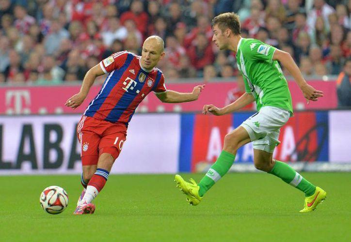 Arjen Robben (i), que tuvo un gran Mundial con Holanda, anotó un gol y puso el pase para otro en el triunfo del Bayern sobre el Wolfsburg. (Foto: AP)