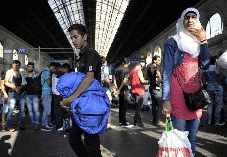 Migrantes esperan para abordar un tren que les llevará a Múnich, en Alemania, en la estación de tren de Keleti, en Budapest, Hungría, el 31 de agosto de 2015. Migrantes con documentos válidos y billetes de tren pueden abordar convoyes internacionales en la terminal. (Tamas Kovacs/MTI via AP)