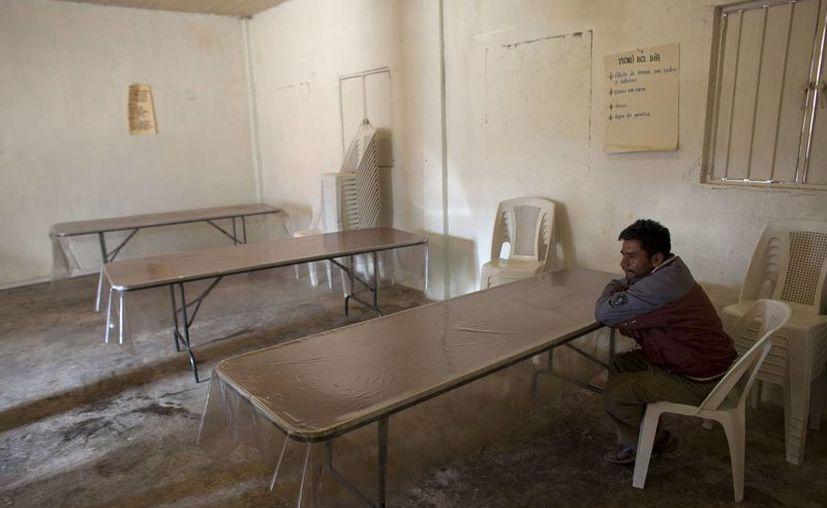 Un hombre sentado en un comedor comunitario en Cochoapa El Grande, donde se supone que debe darse comida gratis a la población. (Agencias)