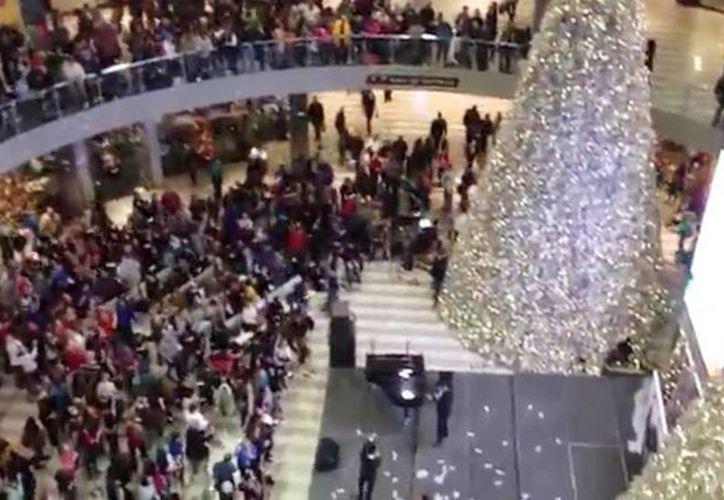 Multitud de personas recibieron con alegría los billetes que cayeron del <i>cielo</i> en un centro comercia de E.U. (Milenio Novedades)