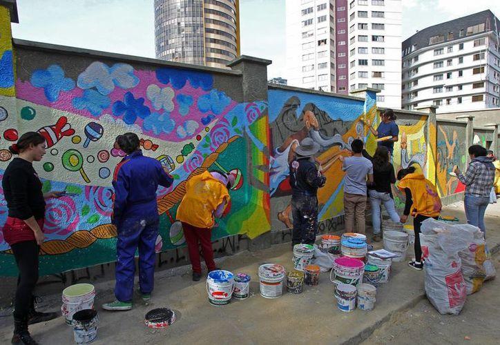 Funcionarias de la alcaldía pintan murales en una calle de La Paz, Bolivia, este 4 de julio de 2014. (EFE)
