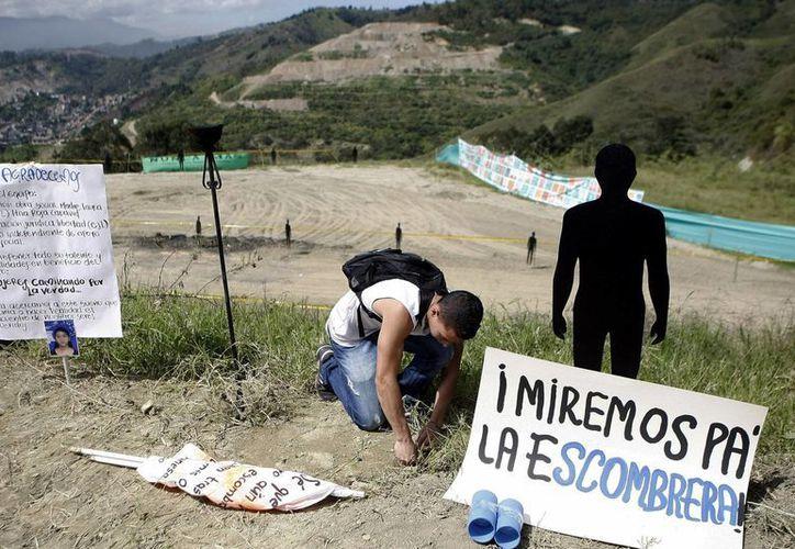 Familiares de víctimas asisten a un acto simbólico al inicio de la mayor excavación forense del país para encontrar a centenares de víctimas de la violencia sepultadas bajo montañas de escombros en Medellín. (EFE)