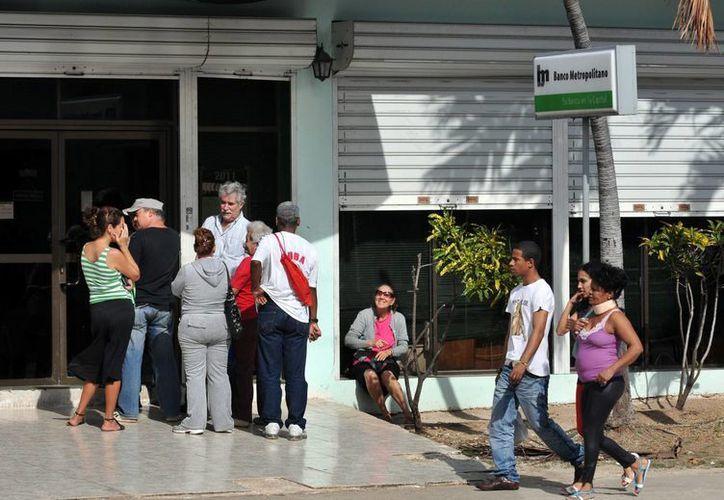 Algunas personas hacen fila en la puerta de un banco en La Habana. (Archivo/EFE)