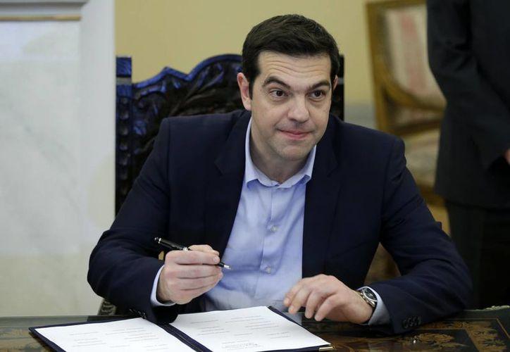 Imagen del primer ministro Alexis Tsipras al firmar un protocolo después de la ceremonia de juramento de su gabinete en el Palacio Presidencial de Atenas. (Agencias)
