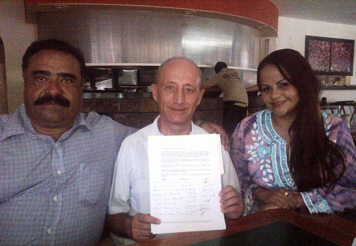 Marciano Toledo Sánchez, ex presidente municipal, y la ciudadana Lorena Moreno, posan junto al padre Pablo, quien muestra la carta que será enviada al Papa.  (Daniel Pacheco/SIPSE)
