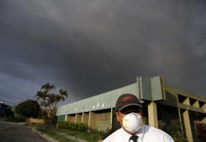 Un hombre usa un tapabocas para evitar respirar la ceniza que cae en la ciudad de San José, capital costarricense. (EFE)