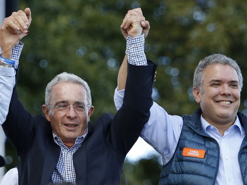 Colombia's former President Alvaro Uribe stands between Ivan Duque, presidential candidate for Democratic Center party, right, and his running mate Martha Lucia Ramirez during a campaign rally in Bogota, Colombia. (AP)