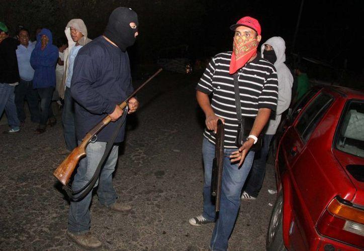 Buscan que los ciudadanos armados colaboren con las fuerzas del gobierno. (Archivo/Notimex)