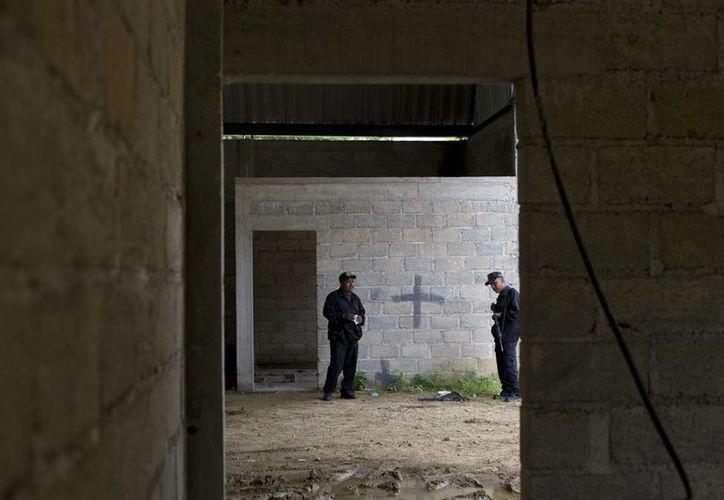 La policía estatal se encuentra en la bodega en Tlatlaya, Estado de México, donde murieron 22 personas en un enfrentamiento con el Ejército. (Agencias)