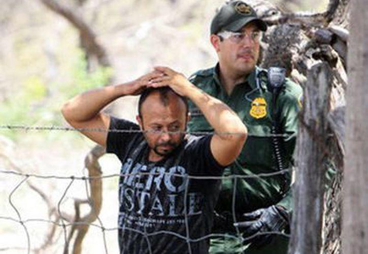 Un hombre es detenido por agentes de la Patrulla Fronteriza el 25 de junio de 2013 en un campo de Edinburg, Texas. (Agencias)