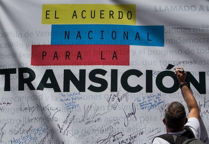 Un participante firma una pancarta este sábado en Caracas, Venezuela. (EFE)