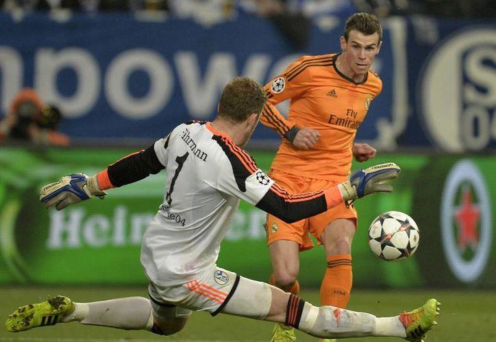 El galés Gareth Bale supera al arquero Ralf Faehrmann, del Schalke, que en realidad tuvo suerte de perder nada más 6-1. (Agencias)