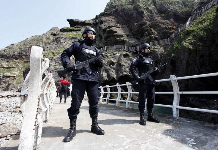 Guardias surcoreanos vigilan el pasado viernes un acceso en uno de los islotes de Dodko, situados entre Corea del Sur y Japón. (EFE)