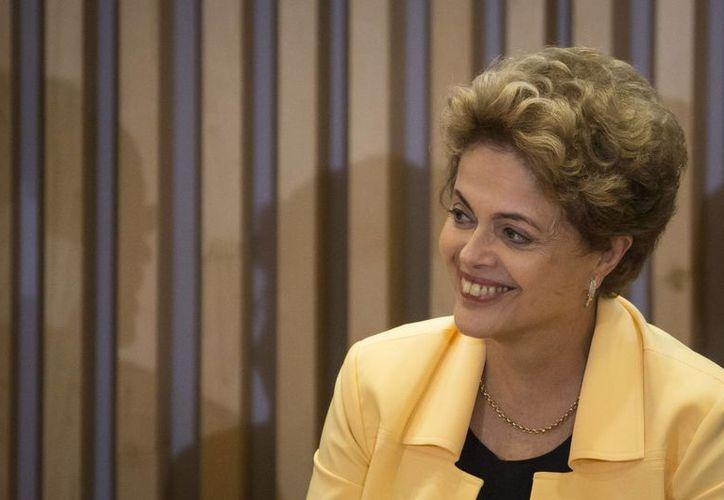 """La presidenta brasileña Dilma Rousseff participa en la ceremonia de firma de un decreto presidencial que da exenciones tributarias a compañías que se sumen a la """"Zona Verde de Libre Comercio"""", el viernes 18 de diciembre del 2015, en el palacio presidencial Planalto en Brasilia. Rousseff obtuvo una victoria importante en la Corte Suprema el viernes, en su batalla contra los intentos de destituirla mediante juicio político. (Foto AP/Eraldo Peres)"""