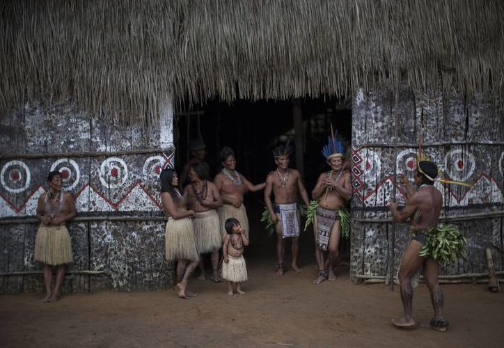 En esta foto del 19 de mayo de 2014, aparecen residentes de varias tribus a la entrada de una casa ceremonial en la comunidad indígena de Tatuyo, cerca de Manaos, Brasil. (Agencias)