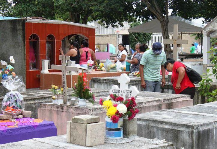 Ayer los miles de visitantes llenaron de color el panteón municipal.  (Daniel Pacheco/SIPSE)