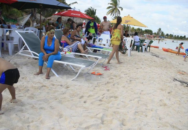 Los turistas no se dejaron intimidar por las lluvias aisladas de este domingo en Mahahual. (Harold Alcocer/SIPSE)