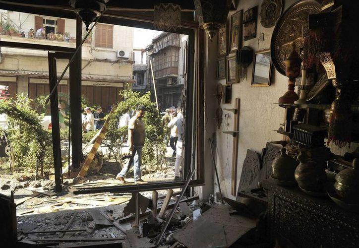 Fotografía distribuida por la agencia de noticias oficial siria SANA que muestra los daños ocasionados en una tienda, tras un atentado suicida en Damasco, Siria. (Archivo/EFE)