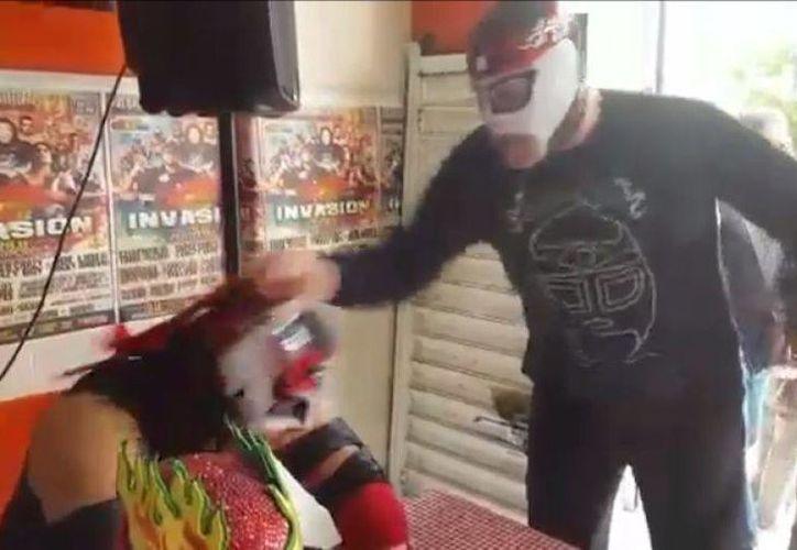 Momento en que Octagón original despoja de su máscara a Octagón Jr., en una firma de autógrafos. (Captura de pantalla)