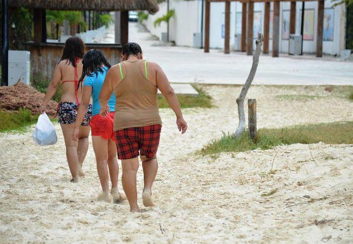 Si bien algunos bañistas salieron del mar para resguardarse de la lluvia, muchos regresaron al cesar las precipitaciones.  (Rafael Acevedo/SIPSE)