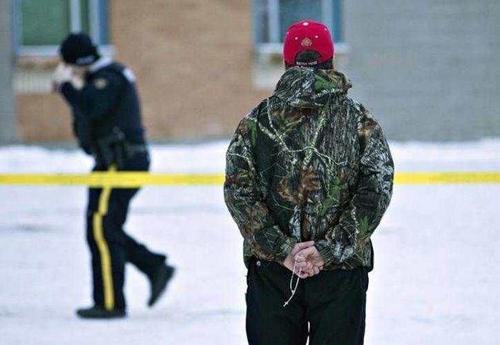 Una persona contempla la escuela comunitaria de La Loche, comunidad en Canadá, donde un tiroteo dejó cuatro muertos y siete heridos, este viernes. (AP)