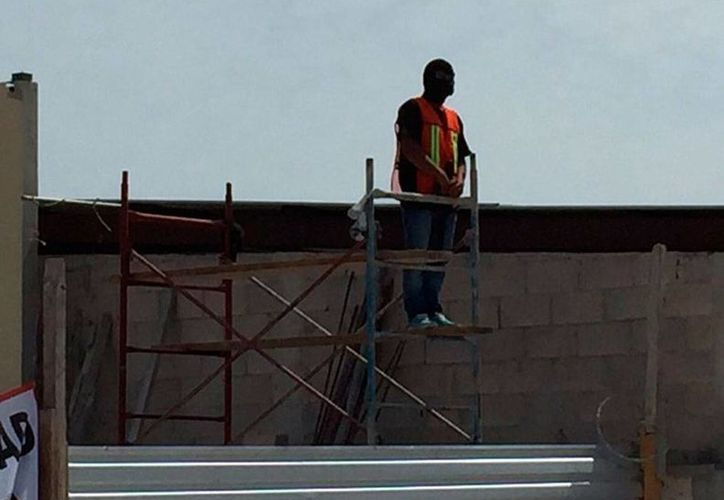 Encapuchados vigilan la construcción de una gasolinera en Progreso. Los vecinos se quejan de que los policías no actúan contra quienes están cuidando el predio. (Óscar Pérez/SIPSE)