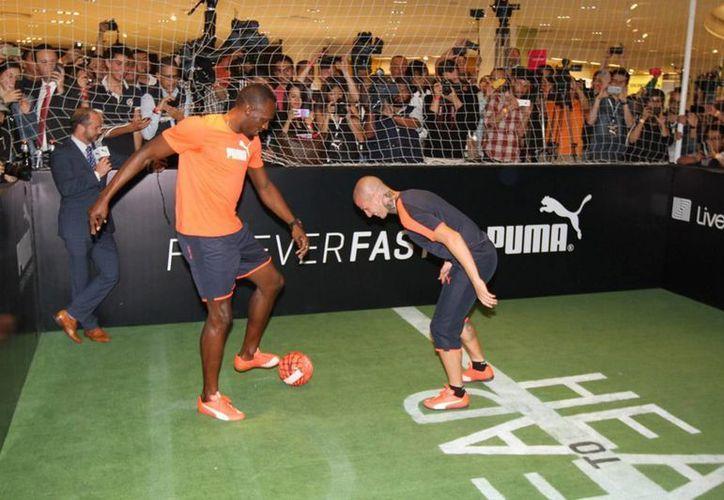 Usain Bolt estuvo este miércoles en México, donde incluso se dio tiempo para jugar una 'cascarita' de futbol. En la foto le acompaña Darío Benedetto, de Águilas del América. (Notimex)