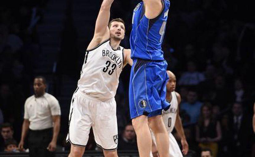 Dirk Nowirzki, de Mavericks, encesta en la prórroga pese a la marcación de Mirza Teletovic (33), de Nets. El basquetbolista alemán ya es uno de los máximos anotadores en la historia de la NBA. (Foto: AP)