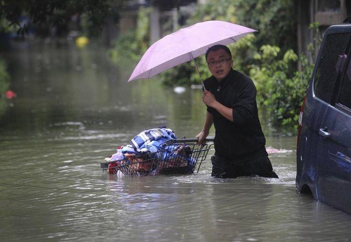 Un hombre empuja un carrito cargado con sus pertenencias en una calle inundada en la ciudad de Tongxiang, en el este de China. (Agencias)