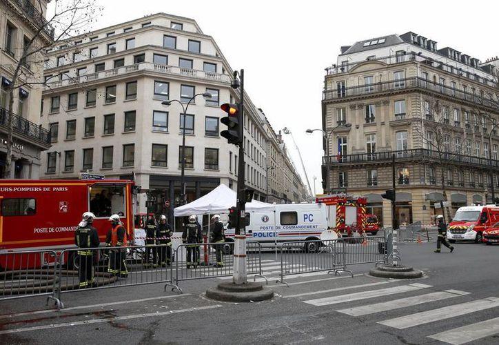 Bomberos trabajan en las labores de extinción de un incendio declarado este martes 17 de enero de 2016 en la última planta del hotel Ritz de París, Francia. (EFE)