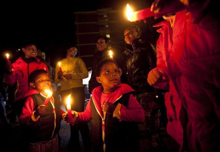 Simpatizantes rezan afuera del hospital donde se encuentra Mandela. (Agencias)