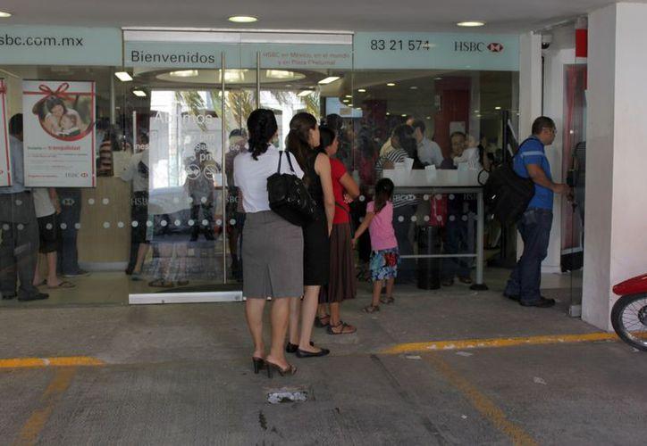 Largas filas de personas esperan en las afueras de instituciones bancarias y cajeros automáticos para retirar sus fondos, desconfían de clonadores. (Enrique Mena/SIPSE)
