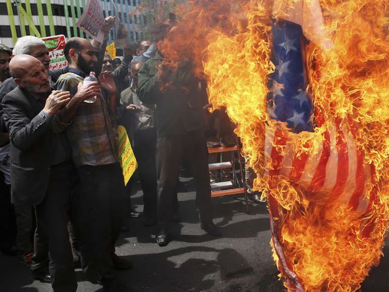 Iranian protestors burn a representation of a U.S. flag. Thousands of Iranians took to the streets in cities across the country to protest U.S. President Donald Trump's decision to pull out of the nuclear deal with world powers. (AP)