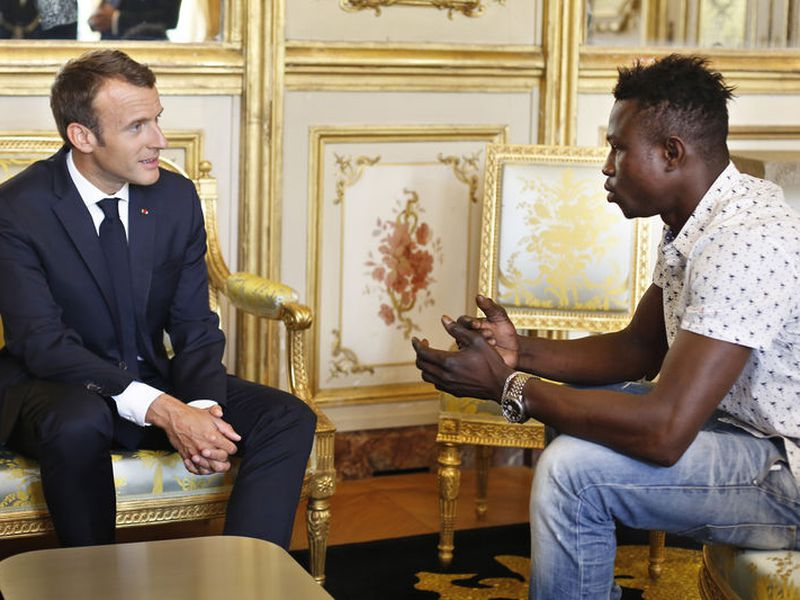 French President Emmanuel Macron, left, meets with Mamoudou Gassama, 22, from Mali, at the presidential Elysee Palace in Paris.