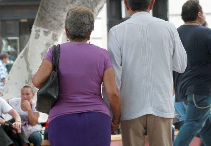 Un juicio de sucesión intestada puede significar dos o tres años, señalan notarios. Imagen de contexto de dos adultos mayores que caminan en la Plaza grande de Mérida. (Milenio Novedades)
