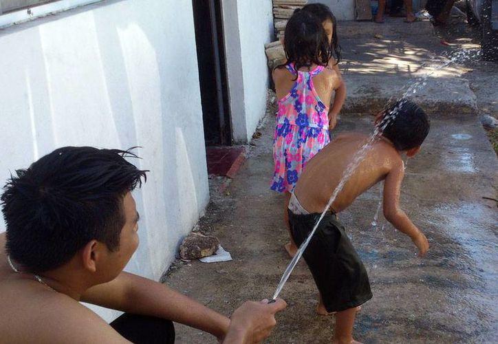 Estos niños se refrescan jugando ante el intenso calor que se registró ayer sábado. (Foto SIPSE)