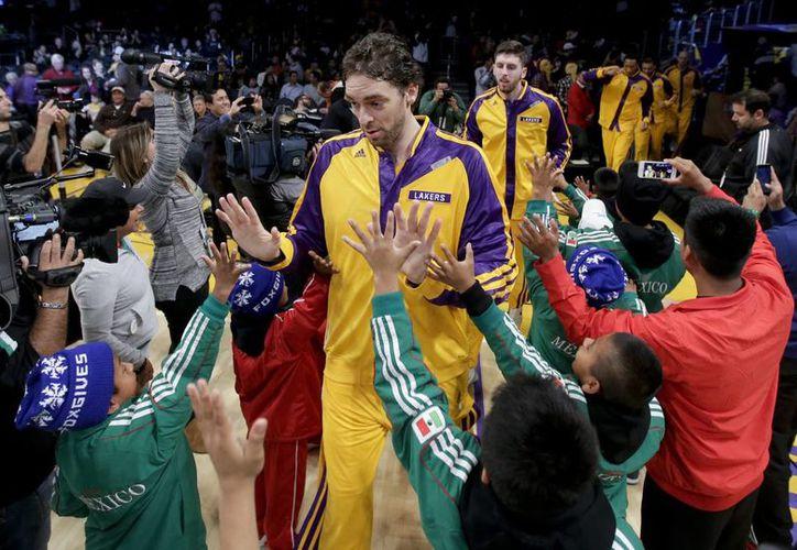<i>Los campeones descalzos de la montaña</i> saludaron a los jugadores de Lakers antes del duelo ante de Timberwolves de Minnesota. En la foto, en primer plano, Pau Gasol. (Agencias)