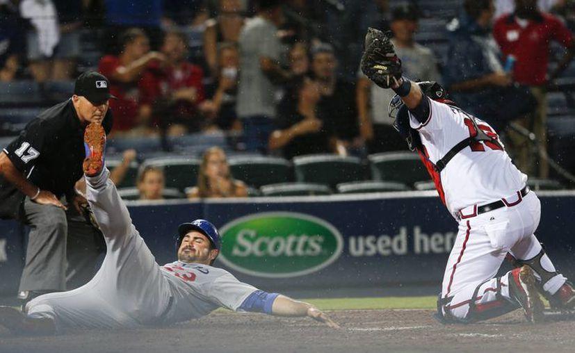 El angelino Adrian Gonzalez (23) se desliza después de ser ponchado en home por el catcher A.J. Pierzynski (15), de Atlanta, que ganó el juego. (Foto: AP)