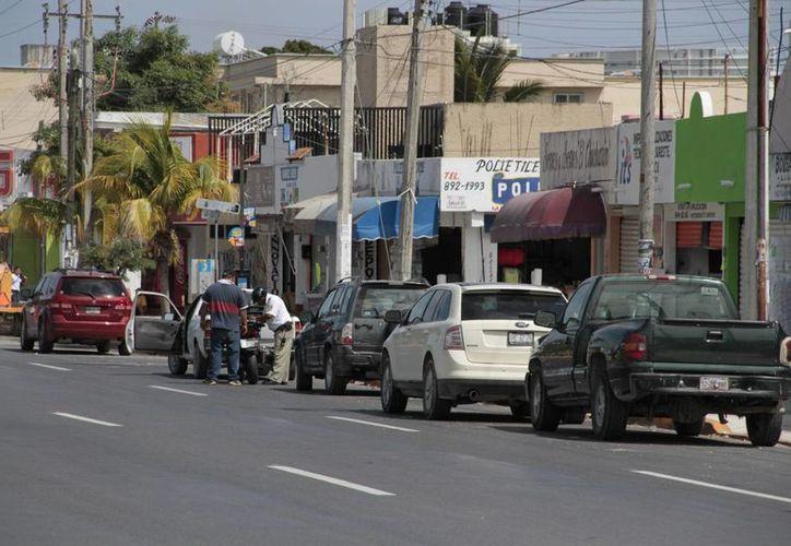 Autos particulares utilizan los carriles laterales en ambos costados de la avenida José López Portillo como estacionamiento. (Tomás Álvarez/SIPSE)
