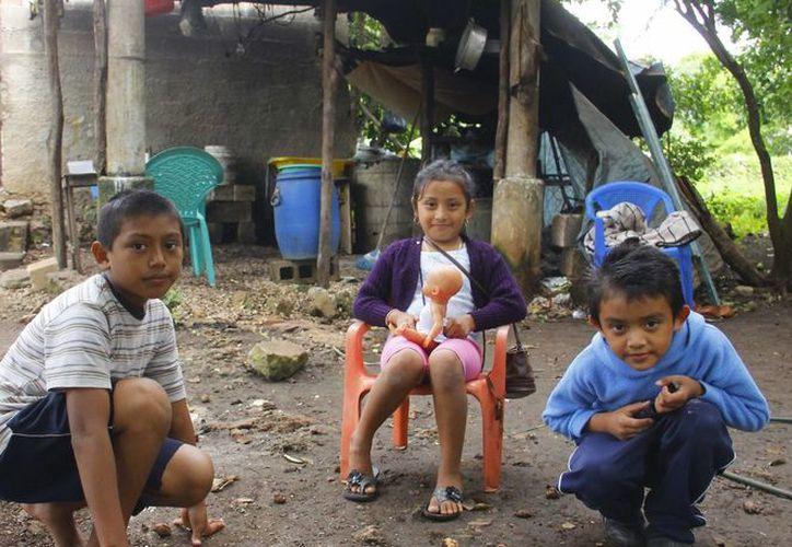Carlitos, acompañado de sus primos Melania Guadalupe y Oswaldo Chan Sulub, comentó que sería una gran alegría que pudiera recibir juguetes nuevos este año. (Juan Albornoz/SIPSE)