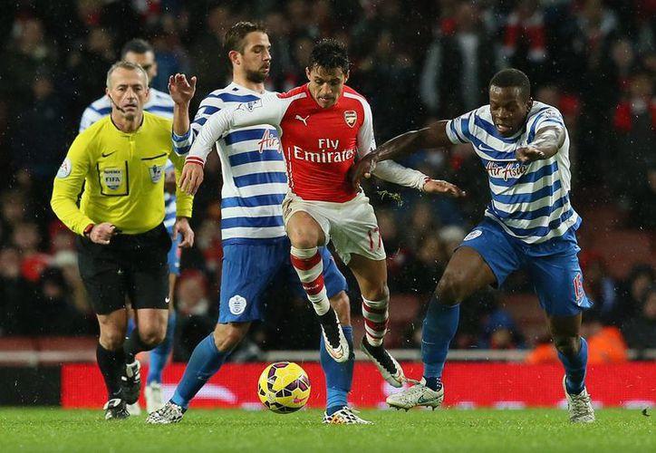 Alexis Sánchez (c) se ha vuelto pieza clave en el buen andar del Arsenal en su primera temporada en el futbol inglés. En la foto se abre paso entre rivales del Queens Park Rangers. (Foto: AP)